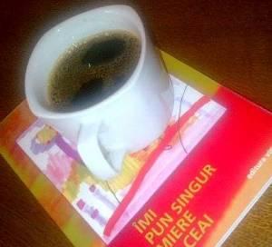 Cană de cafea într-o ceaşcă normală, aşezată pe-o carte. FOTO (cu telefonul): Călin Hera