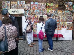 Muzeul Ţăranului Român, de Florii 2014. Picturi naive şi bărbat în costum popular. Foto cu telefonul: Călin Hera