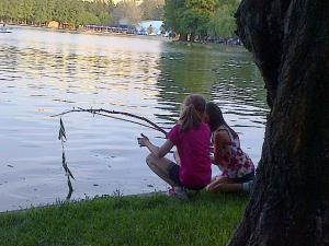 """Vedere din Bucureşti. Două fetiţe """"pescuiesc"""" la malul lacului IOR. Foto: Călin Hera (cu telefonul)"""
