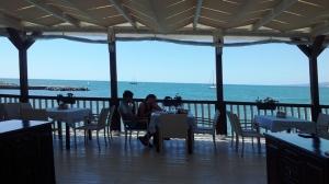 Faleza Balcic. Oameni la masă la o terasă ridicată pe picioare de lemn, deasupra mării.  Foto cu telefonul: Călin Hera