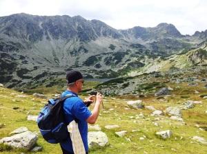 Munții Retezat. Turist fotgrafiind lacul Bucura. Foto cu telefonul: Călin Hera