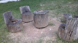 Scaune din lemn și o masă-butuc așezate întru oleacă de odihnă lângă Mănăstirea Arnota, județul Vâlcea. Foto cu telefonul: Călin Hera