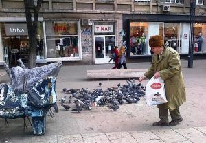 Vârstnic hrănind porumbei în Piaţa Romană, Bucureşti. Foto cu telefonul: Călin Hera