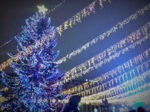 Vedere din București. Înghesuială de weekend, dâre de lumină și brad în Târgul de Crăciun, zona statuilor de la Universitate. Foto cu telefonul: Călin Hera
