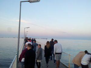 Oameni adunați împreună pe Pasarela de la Mamaia, întinsă peste Marea Neagră, aici foarte albă în amurg. Foto: Călin Hera