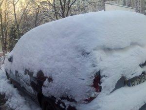 Mașină roșie sub zăpadă albă. Foto: Călin Hera